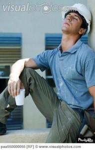 Construction worker sitting on ledge, leaning head back, eyes closed, taking break